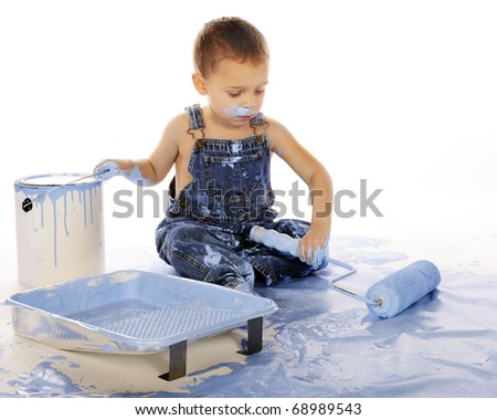 An adorable preschooler painting a floor blue with a roller.  Isolated on white. - stock photo