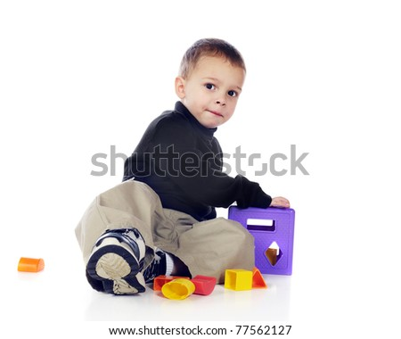 An adorable preschooler playing with a colorful 3-D puzzle.  Isolated on white.