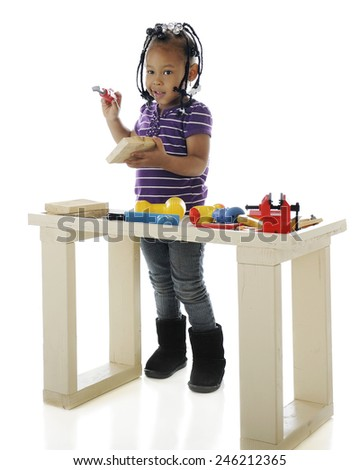 An adorable preschooler playing with toy tools on a child-sized workbench.  On a white background.