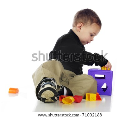 An adorable preschooler putting pieces into a puzzle cube.  Isolated on white.