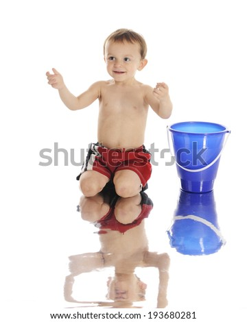 An adorable preschooler ready to catch a beach ball (not shown) as he kneels at the water's edge in his swim trunks.  On a white background. - stock photo