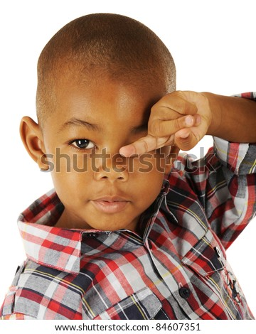 An adorable preschooler rubbing his eyes while pointing with his finger.  On a white background. - stock photo