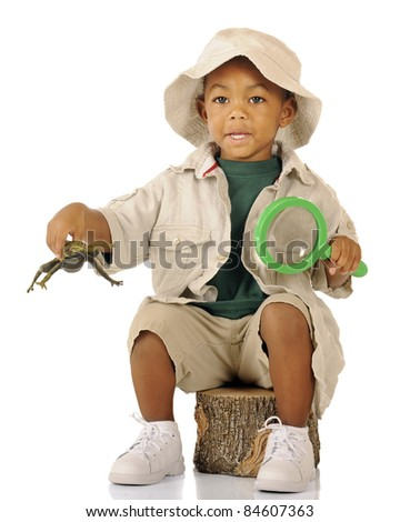 An adorable preschooler sitting on a tree stump in safari attire.  He's hopping a frog in one hand (with motion blur) and holding a magnifying glass in the other. - stock photo