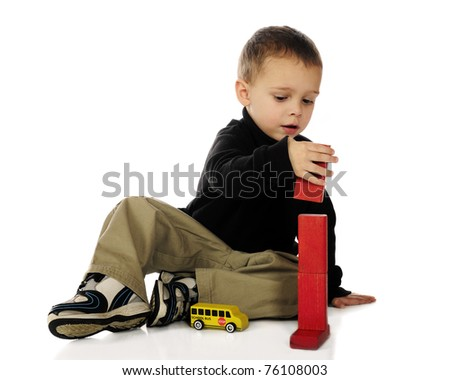 An adorable preschooler stacking red blocks end to end.  Isolated on white. - stock photo