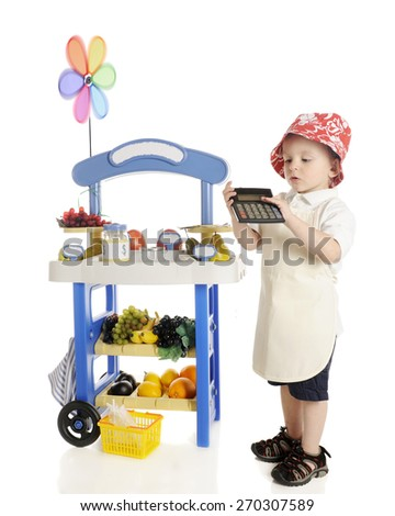 An adorable preschooler standing by his fruit stand while calculating his profits to show the viewer.  The stand's signs are left blank for your text.  On a white background. - stock photo