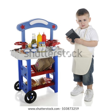 An adorable preschooler standing by his hot dog stand calculating the cost of your order.   The stand's signs left blank for your text.  On a white background. - stock photo