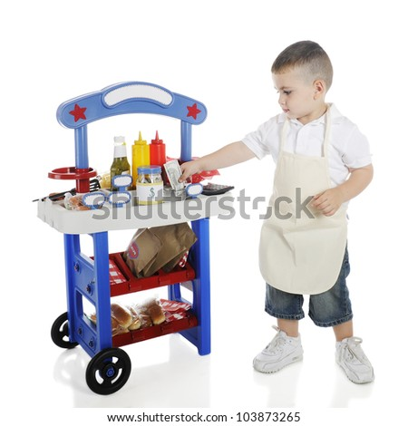 An adorable preschooler storing his hot dog stand income in a money can.  The stand's signs are left blank for your text.  On a white background.