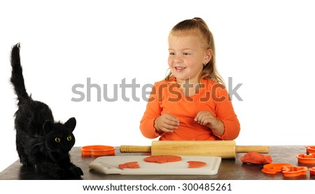 An adorable preschooler taking a break from cutting Halloween cookies out of modeling dough to look at an ugly black cat. - stock photo
