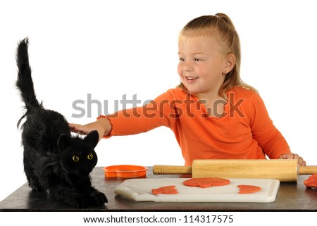 An adorable preschooler taking a break from cutting out Halloween modeling clay cookies to pet a scary black cat. - stock photo