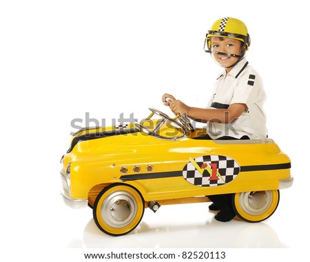 "An adorable preschooler wearing a helmet while ""racing"" in a bright yellow pedal car.  Isolated on white."