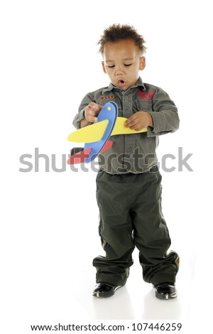 An adorable preschooler wearing an air force outfit impressed with the toy plane he holds.  On a white background.