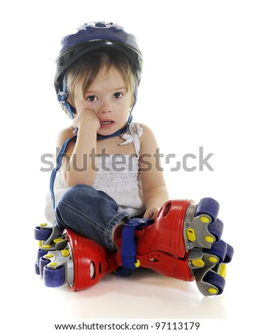 An adorable preschooler weepy because her plastic roller blades made her fall.  On a white background. - stock photo
