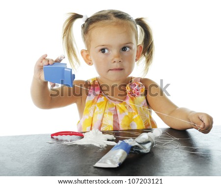 An adorable preschooler who has made a mess loading her own toothbrush with tooth paste, and is pulling out all the floss.  On a white background. - stock photo