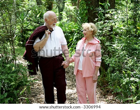 An adorable senior couple walking through the woods hand in hand. - stock photo