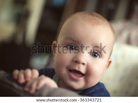 An adorable, smiling baby looking at camera.Close up head shot of a caucasian baby boy. - stock photo