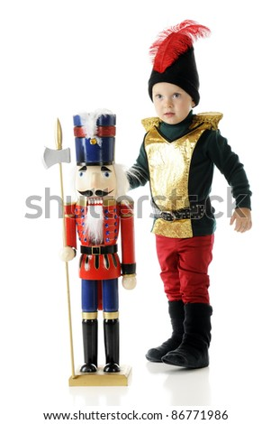 An adorable toddler boy dressed as a nutcracker, standing beside a large wooden nutcracker.  On a white background. - stock photo