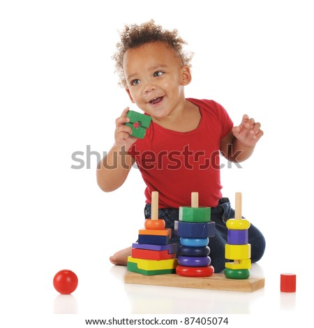 An adorable toddler boy happily assembling a colorful stacking puzzle.  On a white background.