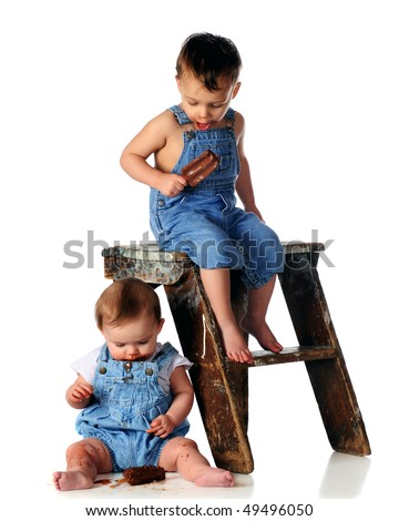 An adorable toddler boy sitting on an old step stool looking down on his baby sister whose dropped her fudgecycle.  Isolated on white.