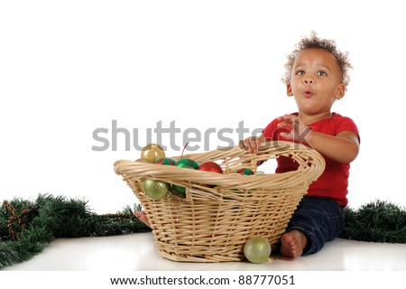 An adorable toddler delighted with a basketful of Christmas bulbs.  One a white background. - stock photo