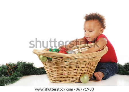 An adorable toddler digging into a basketful of Christmas bulbs.  On a white background. - stock photo