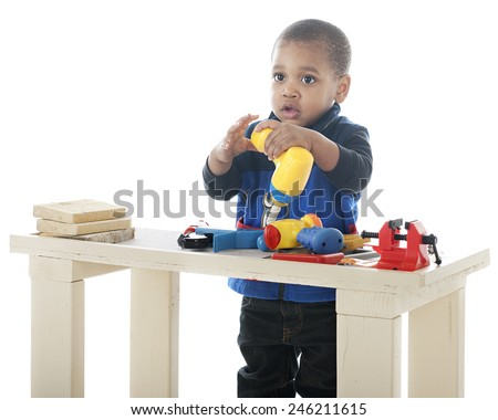 "An adorable toddler drilling with a toy ""electric drill.""  Other tools nearby on his tool bench.  On a white background. - stock photo"