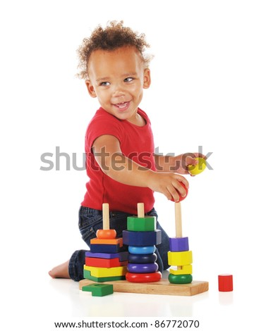 An adorable toddler happily assembling a stacking colorful shapes on a stacking toy.  On a white background.