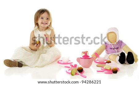 An adorable toddler happily having a party with her dolly.  On a white background. - stock photo