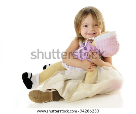 An adorable toddler happily hugging her baby doll.  On a white background. - stock photo