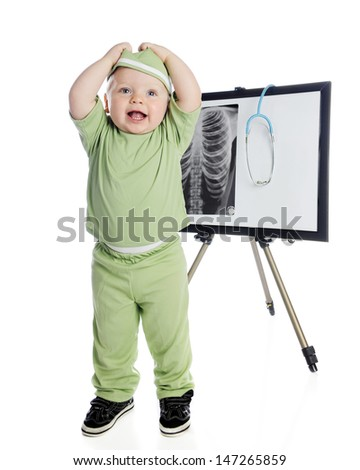An adorable toddler happily pulling off his hat while standing in green scrubs in front of an easel displaying a human chest and stethoscope.  On a white background. - stock photo