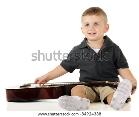 An adorable toddler looking up as he plucks the strings of a classic guitar.  Isolated on white.