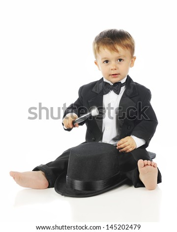 An adorable toddler sitting barefoot in his black tuxedo while happily drumming on his top hat.  On a white background.  Motion blur on his drumstick.