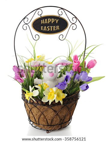 An adorable toy rabbit surrounded by colorful spring flowers, all in a wire basket with a welcome sign on the handle overhead. - stock photo