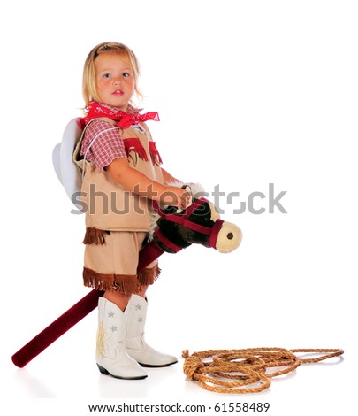 An adorable two-year-old cowgirl riding a stick-horse.  Isolated on white. - stock photo