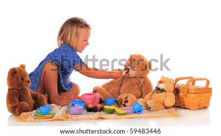 An adorable two-year-old happily feeding her Teddy bear while hosing a picnic for 3.  Isolated on white. - stock photo