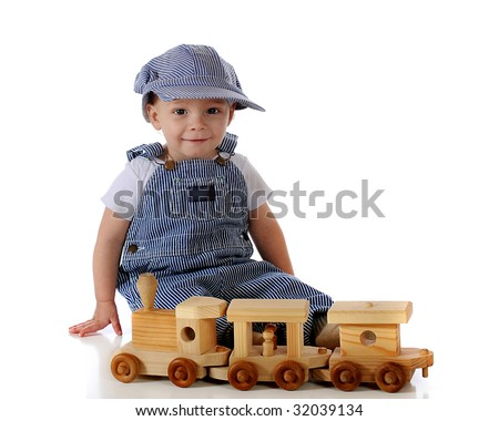 An adorable year-old baby dressed as a RR engineer while playing with a toy wooden train.  Isolated on white. - stock photo