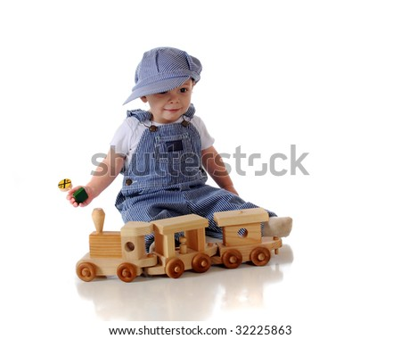 An adorable year-old baby dressed in engineer overalls and cap playing with a wooden train and RR sign.  Isolated on white.