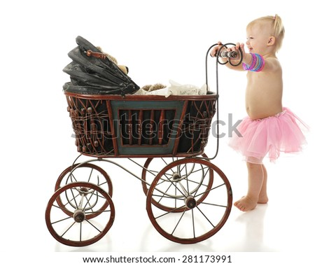 An adorable 2-year-old barefoot in a pink tutu happily taking her Teddy bear for a walk in an old buggy.  On a white background. - stock photo