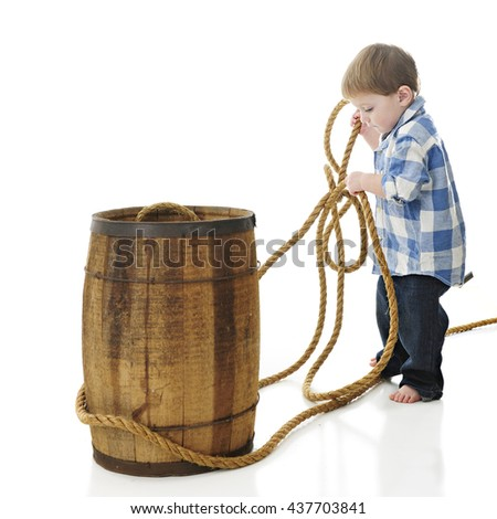 "An adorable 2-year-old ""cowboy"" pulling rope around a rustic old barrel.  On a white background."