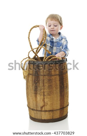 "An adorable 2-year-old ""cowboy"" removing rope from inside a rustic old barrel.  On a white background."