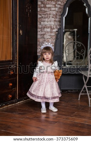 An adorable 2-year-old girl with her toy bear is sad. Portrait Little Princess in full in the interior - stock photo