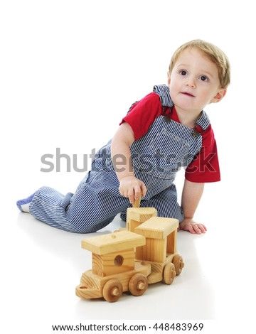 An adorable 2-year-old in engineer overalls looking up as he plays with a toy wooden train on the floor.  On a white background.