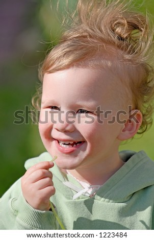 An adorable 2 year old laughs as her hair flies up in the wind. - stock photo