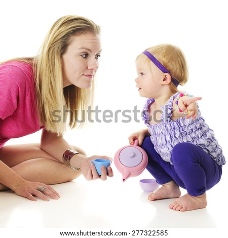 An adorable 2-year-old looking at her mommy as she points in another direction.  On a white background. - stock photo