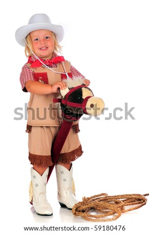 An adorable 2-year-old playing cowgirl while riding a stick horse.  Isolated on white. - stock photo