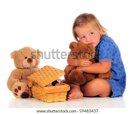An adorable 2-year-old squeezing her Teddy bear with another bear and small, opened picnic basket nearby.  Isolated on white. - stock photo