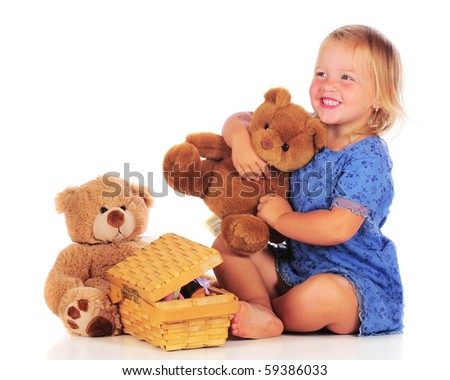 An adorable 2 year-old with teddy bears preparing to have a picnic with them.  Isolated on white. - stock photo