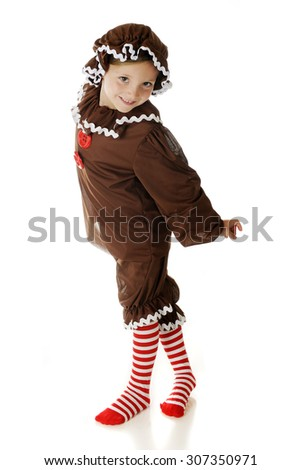 """An adorable young elementary """"Gingerbread Girl"""" twisting around with a smile in her dance.  On a white background. - stock photo"""