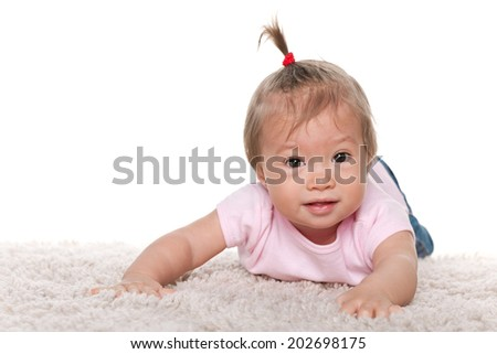 An adorable young girl holds her thumbs up against the white background - stock photo