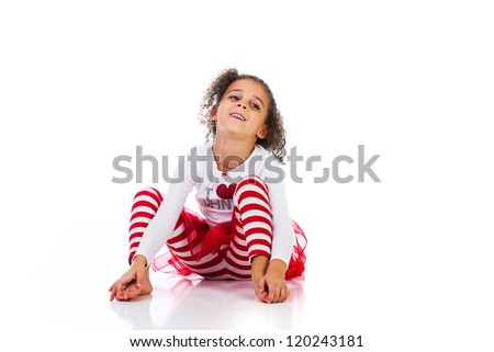 An adorable young girl sitting on the ground - stock photo