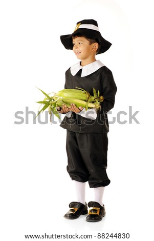 An adorable young Pilgrim boy happily carrying an armful of fresh corn. - stock photo
